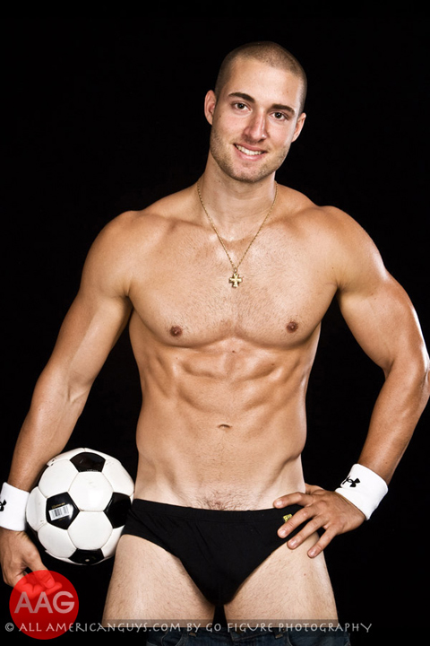 Male fitness model posing with soccor ball