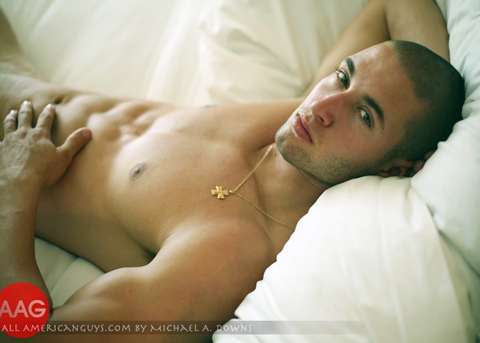 Shirtless male model posing on bed