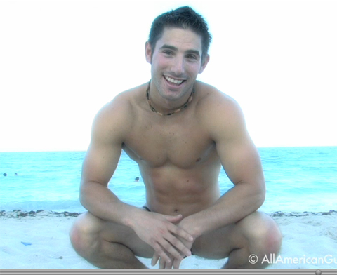 Shirtless male model smiling at the beach