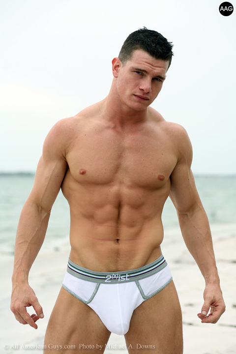 Shirtless male model posing on beach