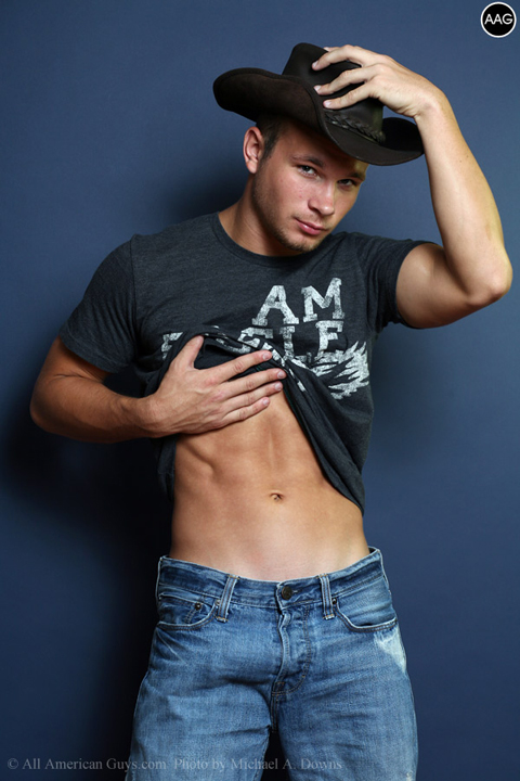 Male model with cowboy hat showing his abs