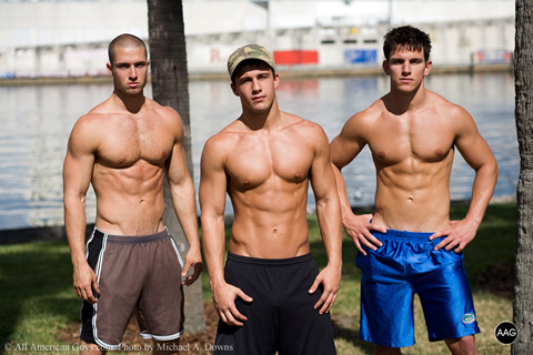 Three shirtless male modles posing by the water